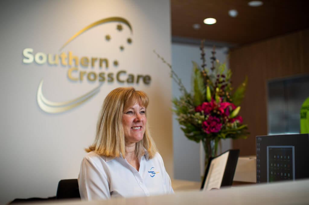 A receptionist is sitting behind a desk at the front counter. the Southern Cross Care logo is placed behind her.